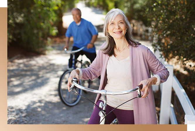Senior Couple riding bikes. The Woman standing beside her bike is in focus